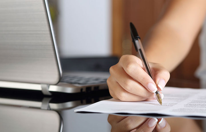 Woman's hand signing documents next to laptop